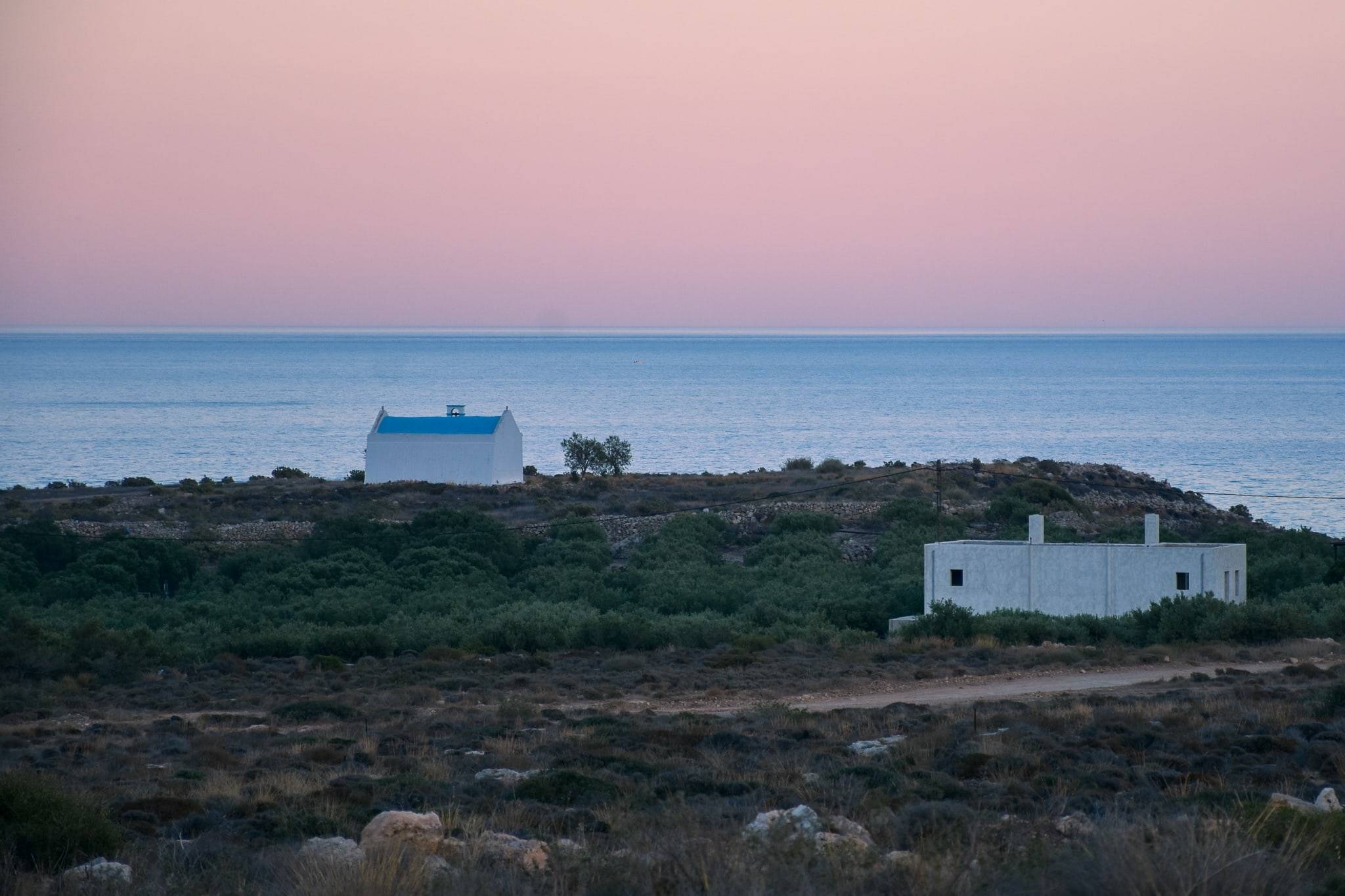 Sunset view from a plot in Xerokampos, east Crete. Sky in the background has a bit of violet color, sea is calm and blue and on the landscape horizon there is a small church of Saint Antonios. It has a white walls and a typical greek blue roof, which makes a perfect contrast with the sea.